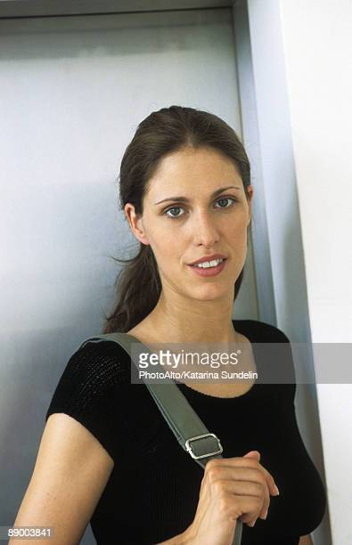 Woman with shoulder bag, smiling at camera