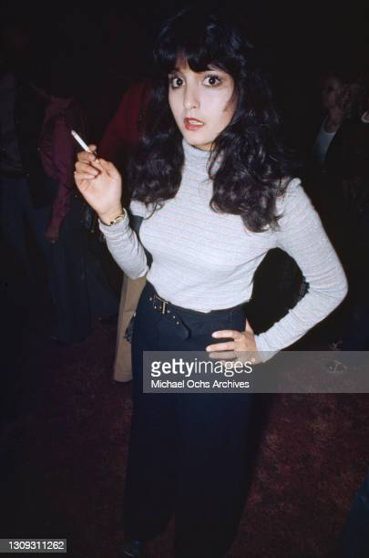 Woman with shoulder-length black hair, wearing a blue, pink and white hooped turtleneck top, smoking a cigarette at an unspecified club, location...