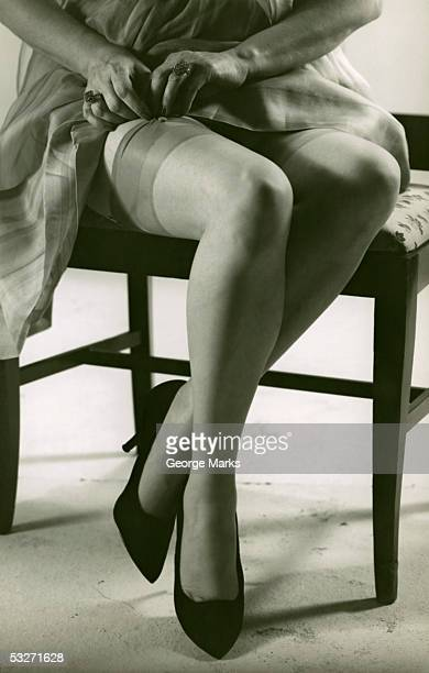 woman with silk stockings fixes garter - garter belts and stockings stock photos and pictures
