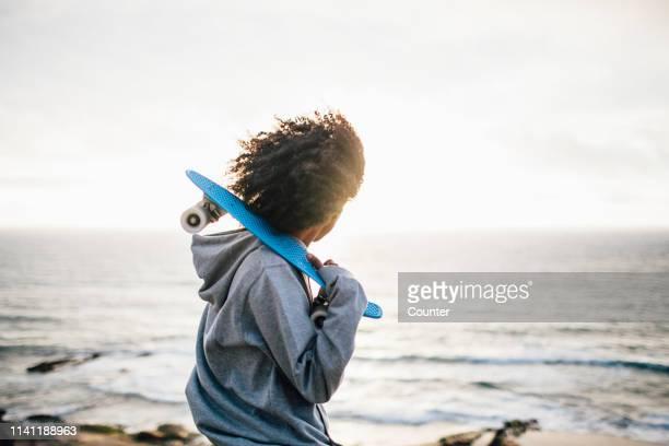 Woman with skateboard overlooking ocean