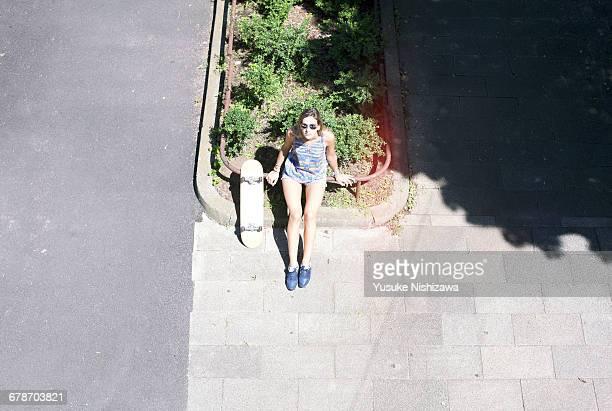 woman with skateboard - yusuke nishizawa stock-fotos und bilder