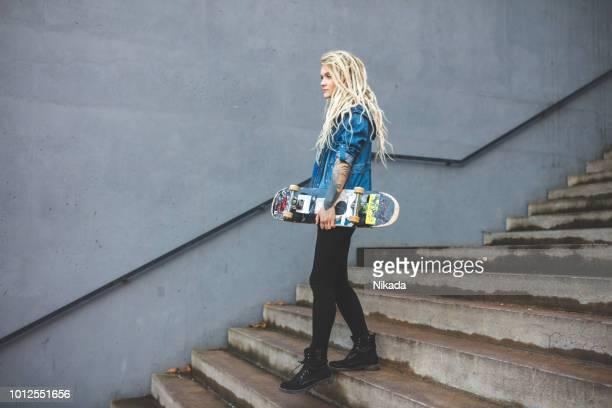 Frau mit Skateboard zu Fuß die Treppe hinunter