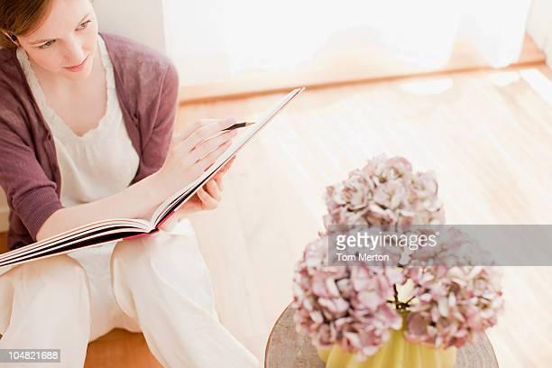 Femme avec Bloc à dessin recherche de fleurs dans un vase