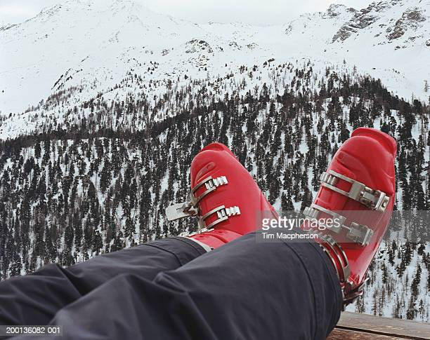 Woman with ski boots, resting legs on ledge, low section