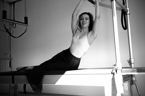 Woman With Skirt Exercising on Pilates Machine - gettyimageskorea