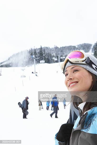 woman with skis at base of mountain near ski lift, smiling, looking up - une seule femme d'âge moyen photos et images de collection