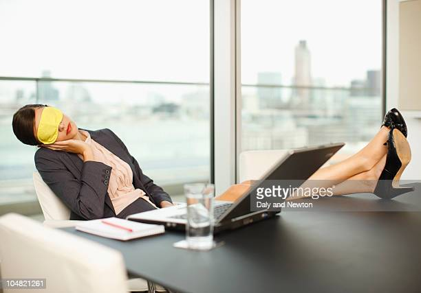 Woman with sleep mask sleeping with feet up on conference room table