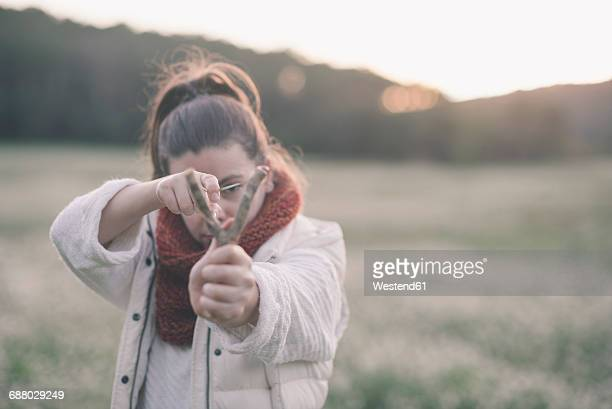 Woman with slingshot in nature aiming with slingshot at viewer