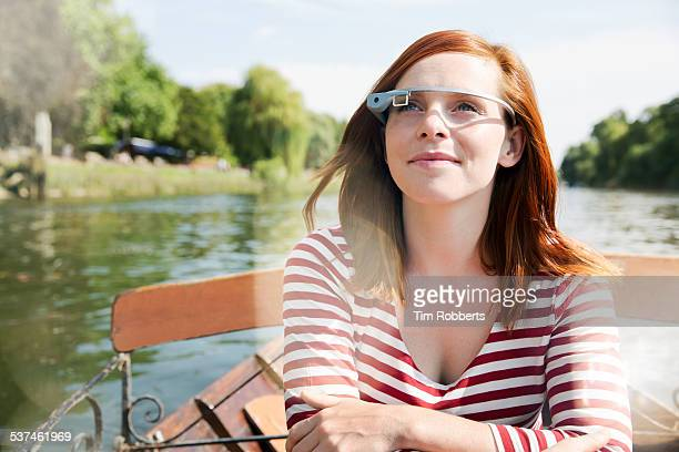 Woman with smart glass in row boat.