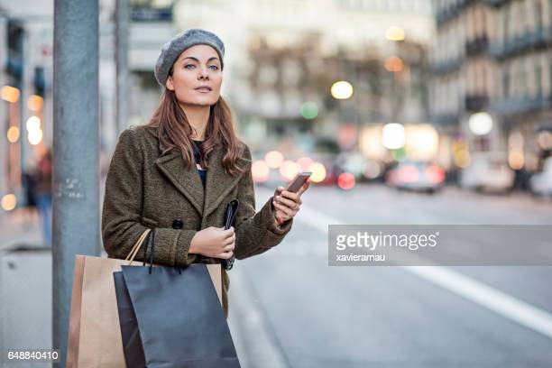 Woman with smart phone and shopping bags at street