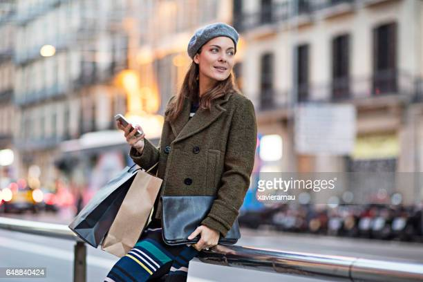 Woman with smart phone and shopping bags by street