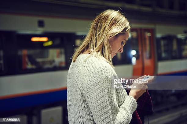 Woman with smart phone in train station