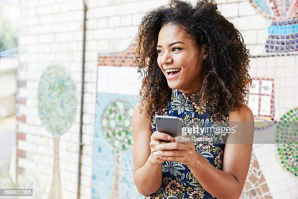 woman with smart phone next to tiled mosaic wall - text stock pictures, royalty-free photos & images