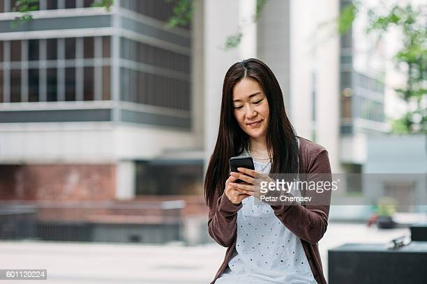 woman with smart phone outdoors - 40代 ストックフォトと画像