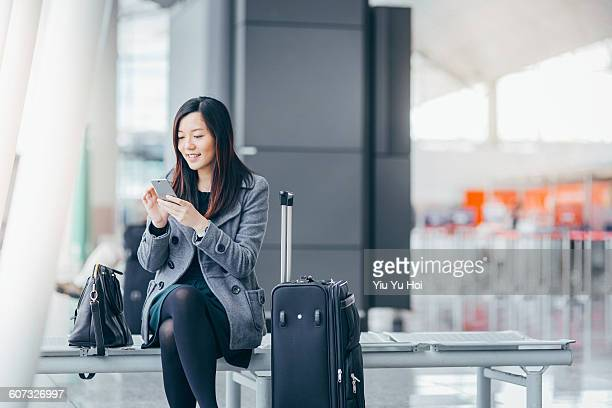 Woman with smartphone and suitcase in airport