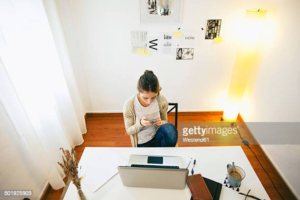 Woman with smartphone at modern home office, elevated view