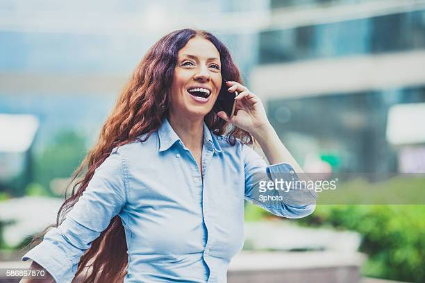 Woman with smartphone going in business block