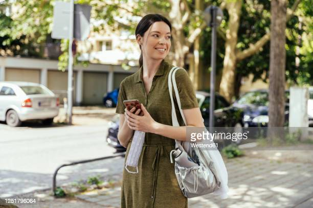 woman with smartphone holding a face mask in her hand while walking to her sports club - shoulder bag stock pictures, royalty-free photos & images