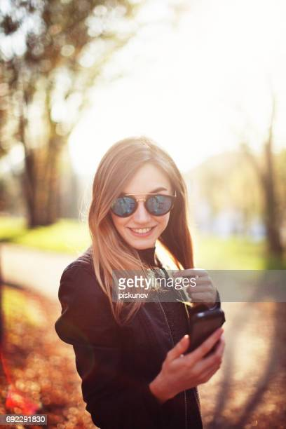 Woman with smartphone in autumn park