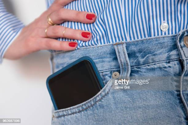 woman with smartphone in jeans pocket - pocket stock photos and pictures