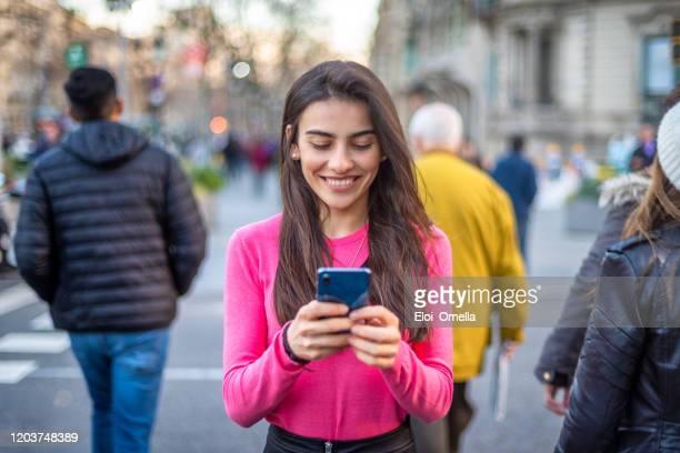 mujer con smartphone en la ciudad - barcelona españa fotografías e imágenes de stock