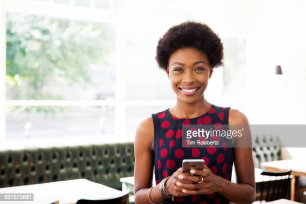 Woman with smartphone looking at camera