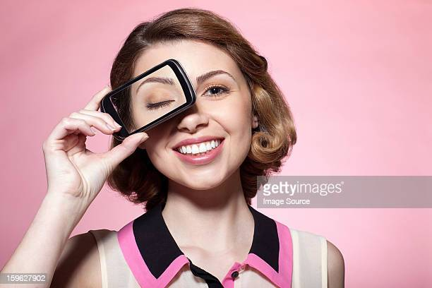 Woman with smartphone over eye