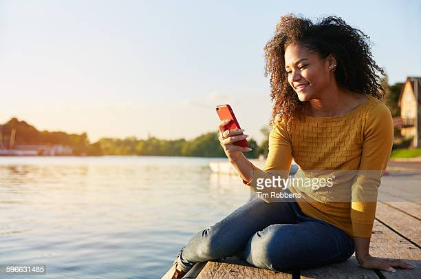 Woman with smartphone sat on river jetty.