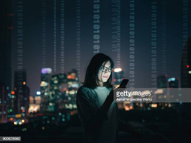 woman with smartphone standing on skyscraper roof - bandwidth stock pictures, royalty-free photos & images