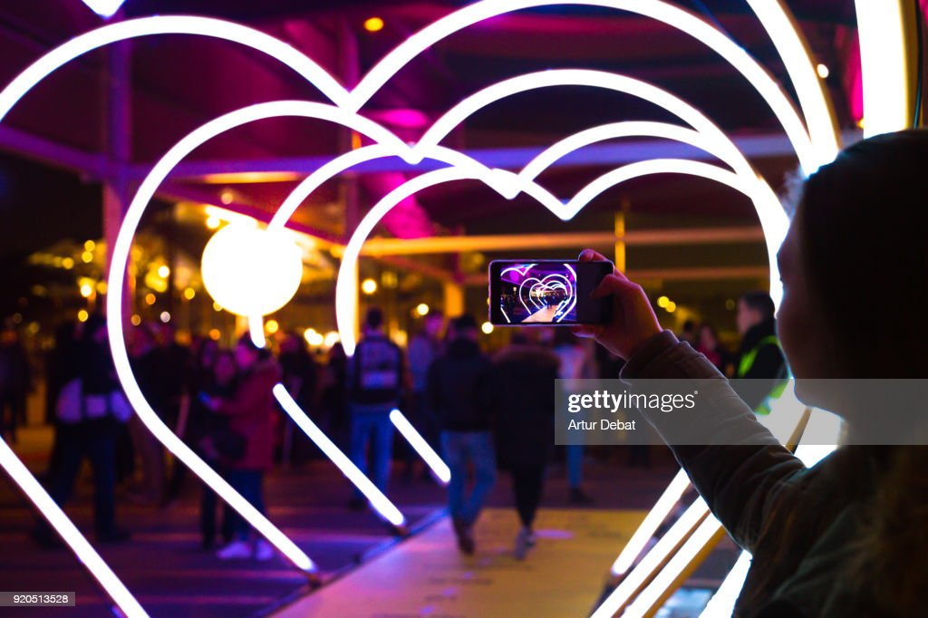 Woman with smartphone taking picture of heart shape lights in the city street. : Foto de stock