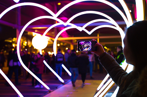 Woman with smartphone taking picture of heart shape lights in the city street. - gettyimageskorea