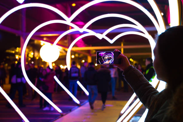 Woman With Smartphone Taking Picture Of Heart Shape Lights In The City Street. Wall Art