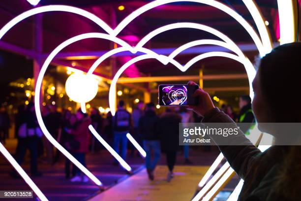 Woman with smartphone taking picture of heart shape lights in the city street.