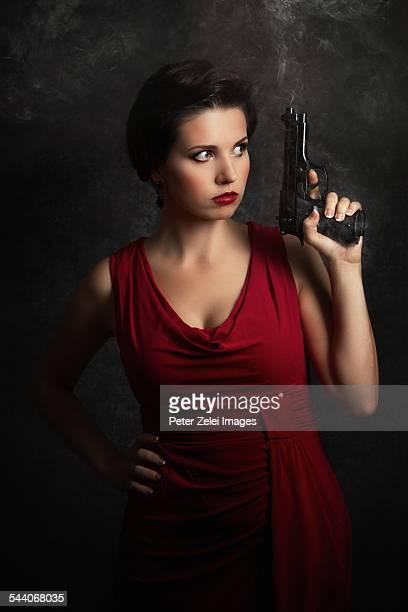 woman with smoking gun - mulher fatal imagens e fotografias de stock