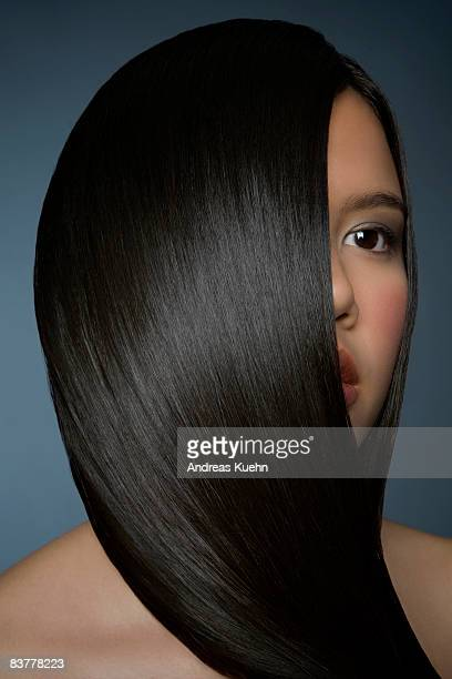 woman with smooth, shiny hair covering face - capelli neri foto e immagini stock