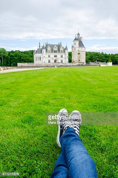 Woman with sneakers lying on grass enjoying the view of Chateau de Chenonceau, Loire Valley, France.