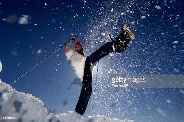 Young woman splashing snow by shoes, low angle view