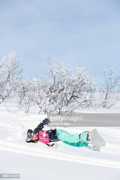woman with snowboard lying on snow - chute ski photos et images de collection