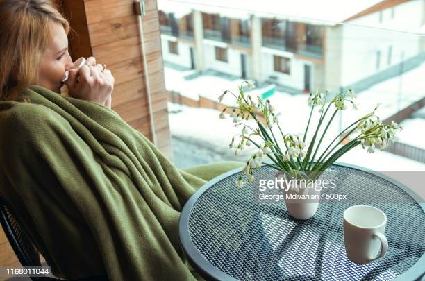 woman with snowdrops and drink mugs on balcony, winter time - snowdrop stock pictures, royalty-free photos & images