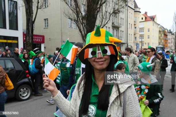 A woman with some glasses with the flag of Ireland and two Irish flags in the hand Around 15000 celebrated St Patrick's day in Munich Germany on 11...