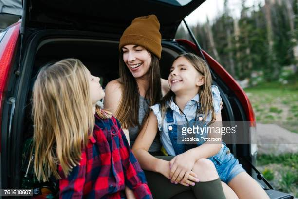 woman with son (6-7) and daughter (8-9) in back of car - white boot stock pictures, royalty-free photos & images