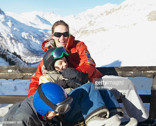 Woman with son and daughter (8-10) relaxing at ski resort, laughing