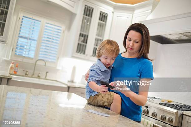 Woman With Son Depositing Check Using Smart Phone