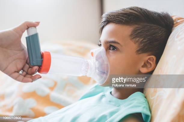 woman with son doing inhalation with nebulizer at home - patient on ventilator stock pictures, royalty-free photos & images