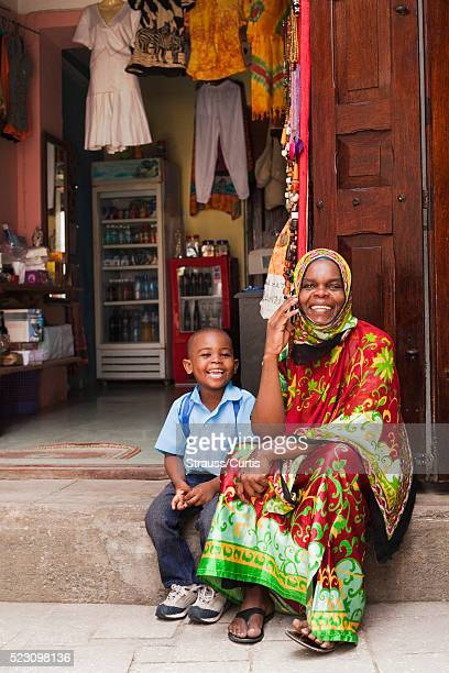 Woman with son (7-9) on phone in East African market