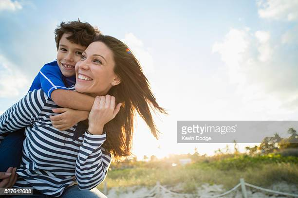 woman with son (10-12) playing at beach - single mother stock pictures, royalty-free photos & images