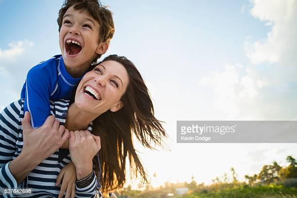 woman with son (10-12) playing at beach - mamma e figlio foto e immagini stock