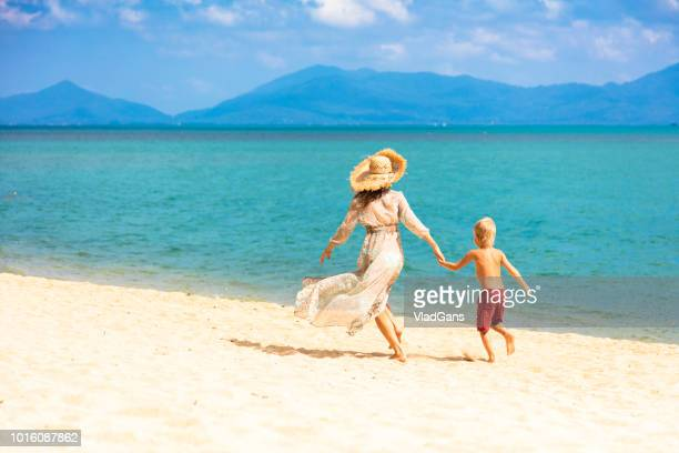 Woman with son running on the beach