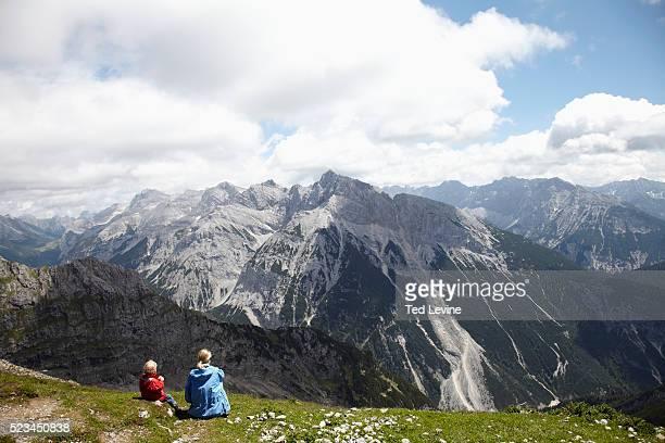 woman with son (4-5) sitting in the grass, watching mountain landscape - mittenwald stock-fotos und bilder
