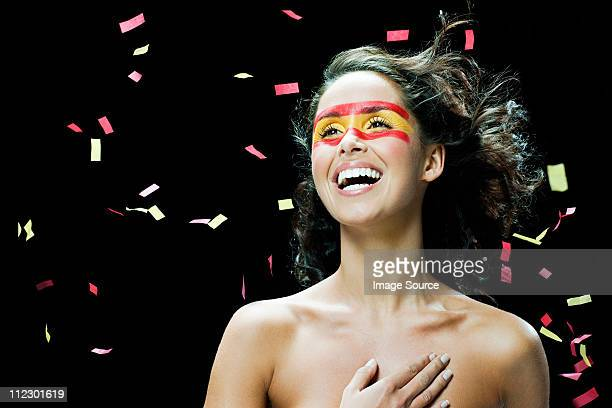 Woman with Spanish flag painted on face, hand on chest and ticker tape